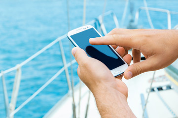 Male hands holding smartphone on sailing