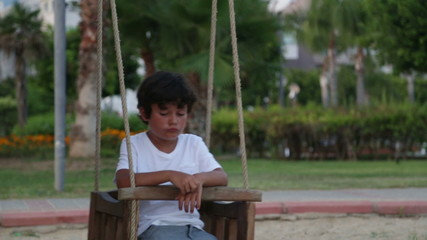 Unhappy lonely  child swinging