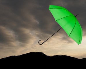 Bad weather background. Green umbrella over stormy sky.