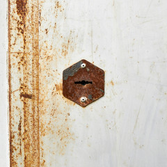 Old rusty metal door with a keyhole