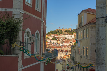 view of a narrow street in the city Lisbon downtown during twili
