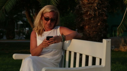 Woman sitting on park bench with her phone