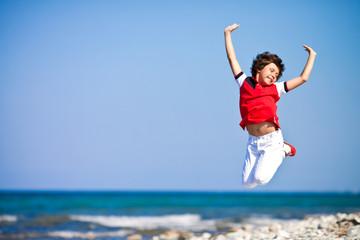 Мальчик в прыжке на берегу моря