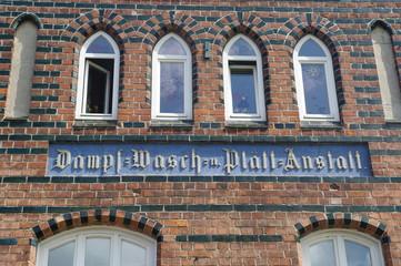 Altes Schild an einer Fassade in Wismar