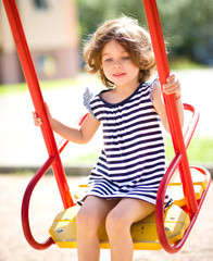 Young happy girl is swinging in playground