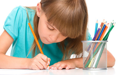 Little girl is drawing using pencils