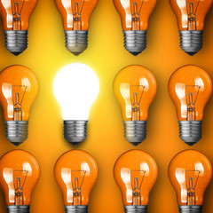 Concept for big idea. Glowing light bulb on orange background