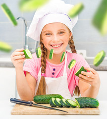 little girl cuts cucumbers