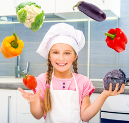 smiling little girl juggle vegetables