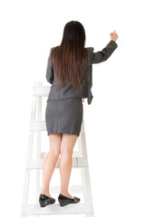 Asian business woman on stairs writing on wall