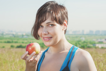 Beautiful fitness woman with apple