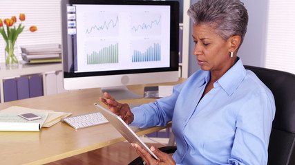 Executive senior black businesswoman working on tablet at desk