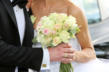 Newlyweds with wedding rose bouquet after wedding ceremony