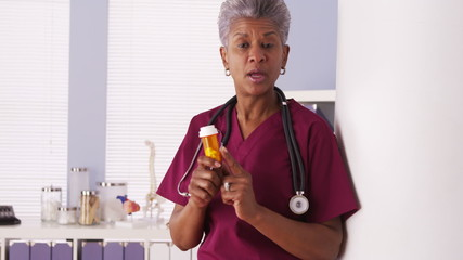 Black senior doctor talking with prescription