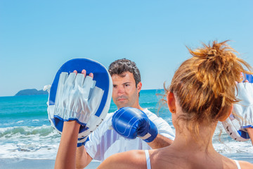 Couple training boxing on the beach