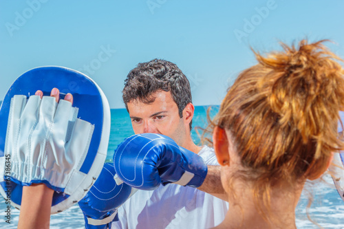 canvas print picture Couple training boxing on the beach
