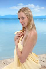Dziewczyna, blondynka w ręczniku kąpielowym nad jeziorem.
