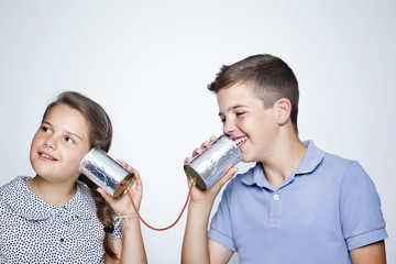 Kids speaking to a can against gray background