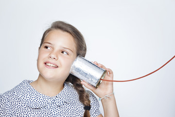 Happy smiling child using a can as telephone against gray backgr