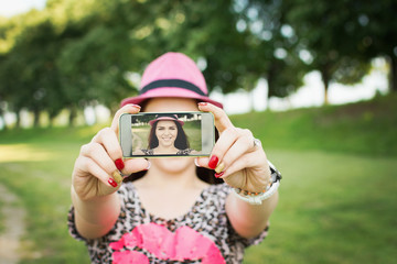Cute young woman taking a selfie in park in summer