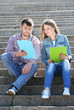 Happy students sitting on stairs in park