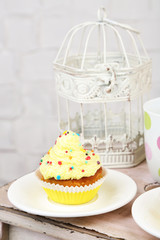 Tasty cup cake with cream on wooden table