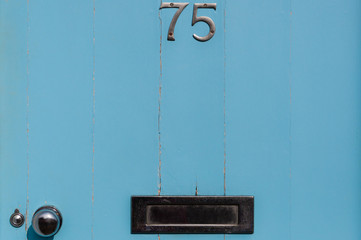 Door number 75 close-up with letter box