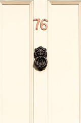 Door number 76 and door knocker close up