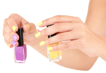 Female hands with stylish colorful nails holding bottle with