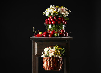Still life with berries and flowers on dark background