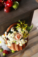 Basket of flowers hanging on wooden shelf close up