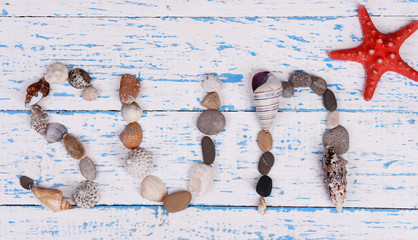 Word sun made from sea shells and stones on wooden background