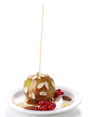 Sweet caramel apple on stick with berries, isolated on white