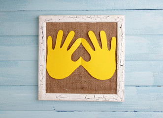 Wooden frame with paper arms on wooden background