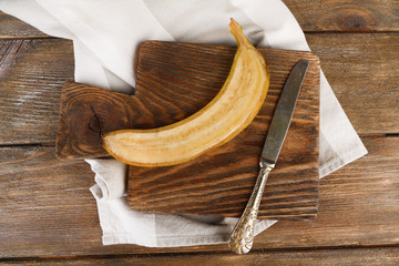 Halved ripe banana on wooden background