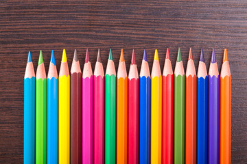multicolored pencils on the brown wooden table