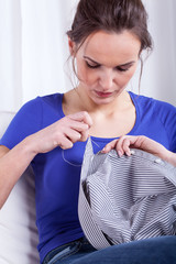 Housewife sewing a shirt