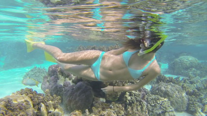 beautiful woman snorkeling in clear blue waters over coral reef
