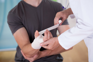 Doctor parceling patient's wrist