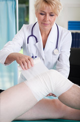 Female doctor parcels patient's knee