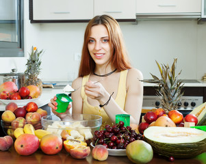 Positive woman making  fruit  salad with yoghourt