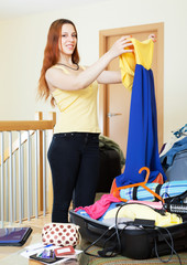 woman packing dress for vacation