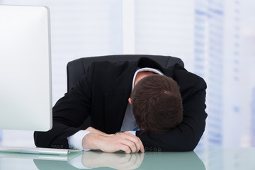 Tired Businessman Resting At Office Desk