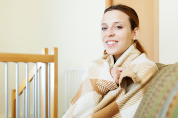 girl warming in plaid at home in winter