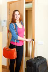 Positive young woman with suitcase near door