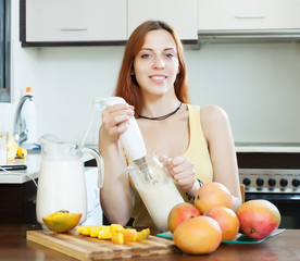 woman making fresh milk beverages with blender from mango