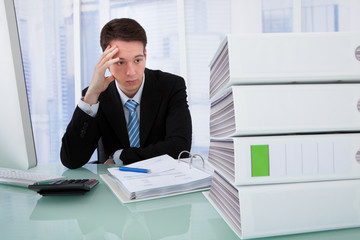 Worried Businessman Looking At Binders On Desk