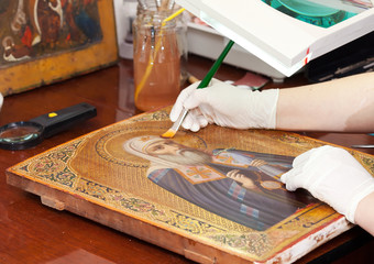 restorer works on ancient icon