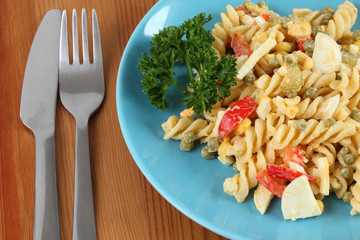 Salad with pasta, tomatoes, parsley, eggs and peas