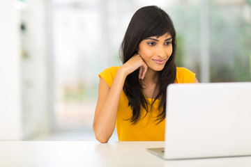 young indian woman looking at the laptop screen